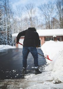 A man shoveling snow in front of his home