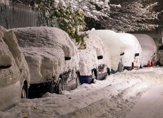 Some cars covered by thick snow.