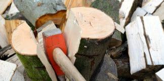 A man using a splitting maul to split a large log.
