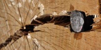 An iron splitting wedge splitting a huge piece of wood.