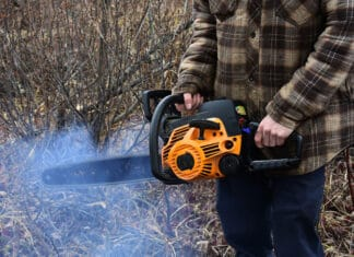 This chainsaw is malfunctioning, emitting smoke while running.
